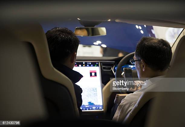 A visitor uses a smartphone as he sits in the driver's seat of a Tesla Motors Inc Model X vehicle at the Combined Exhibition of Advanced Technologies...