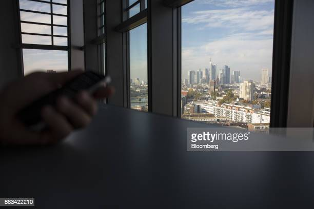 Visitor uses a smartphone as skyscrapers tower over commercial and residential property on the city skyline as seen from the 15th floor pantry area...