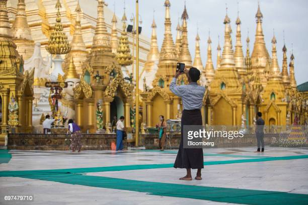 A visitor uses a smartphone to take a photograph at the Shwedagon Pagoda in Yangon Myanmar on Monday June 12 2017 When the country opened to the...