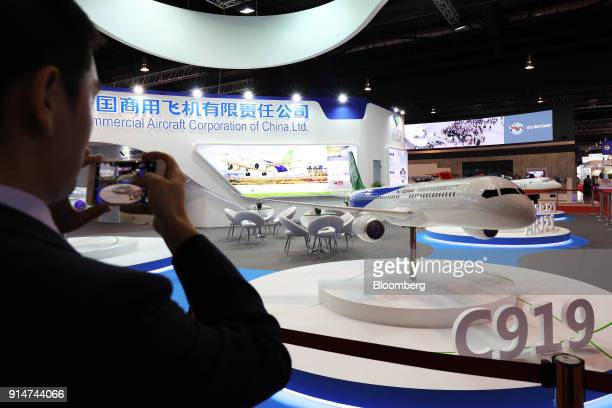 A visitor uses a smartphone to take a photograph of a model of the Commercial Aircraft Corp of China Ltd C919 aircraft at the Singapore Airshow held...