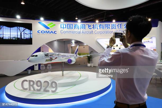 A visitor uses a smartphone to take a photograph of a model of the Commercial Aircraft Corp of China Ltd CR929 aircraft at the Singapore Airshow held...