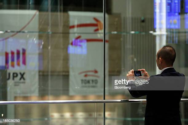 A visitor uses a smartphone to take a photograph of the trading floor of the Tokyo Stock Exchange in Tokyo Japan on Thursday Oct 17 2013 Japanese...