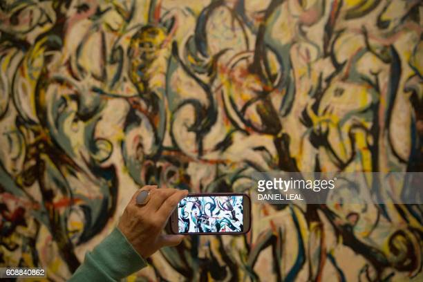 A visitor uses a smartphone to take a picture of a painting entitled ''Mural 1943' by US artist Jackson Pollock during a photocall to promote...