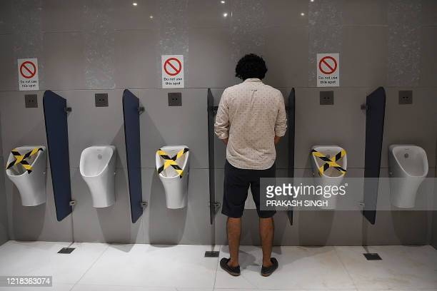 A visitor uses a urinal at a toilet of the Ambience mall as places of religious worship hotels restaurants and shopping malls are allowed to operate...