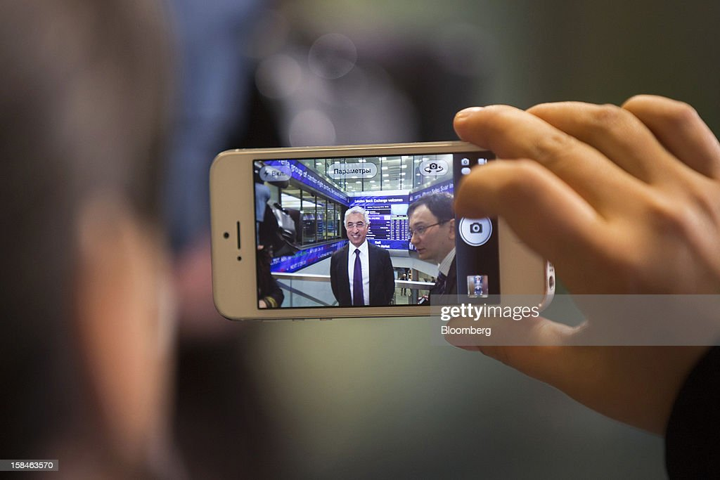 A visitor uses an Apple Inc. iPhone to photograph Veysel Aral, chief executive officer of Kcell, a unit of TeliaSonera AB, center, during the launch of the company's initial public offering (IPO) at the London Stock Exchange in London, U.K., on Monday, Dec. 17, 2012. Kcell, which has 11.6 million subscribers, is the largest operator in Kazakhstan with a subscriber market share of about 48 percent and a revenue market share of 57 percent, Aral said. Photographer: Simon Dawson/Bloomberg via Getty Images