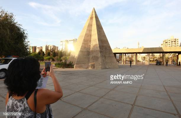 A visitor uses her phone to take a picture of the stone pyramid at the grounds of the Tripoli International Fair close to the seafront of the...