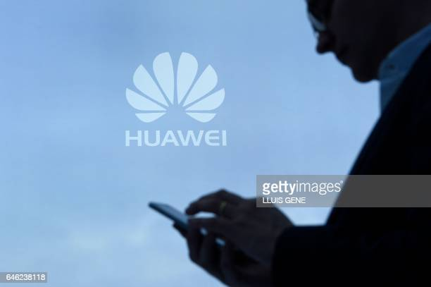 A visitor uses his mobile phone at the Huawei stand on the second day of the Mobile World Congress on February 28 2017 in Barcelona Phone makers will...