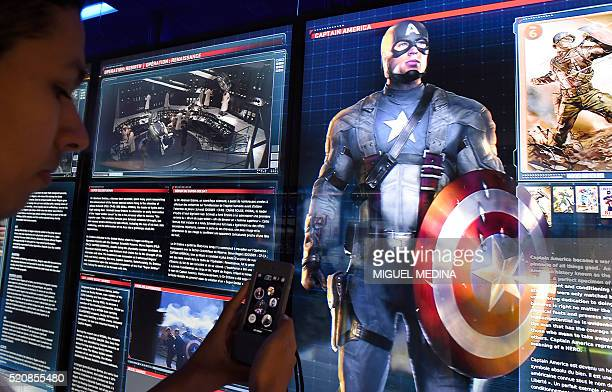 A visitor uses their phone on an interactive display on Marvel Comics superhero Captain America at the Marvel Avengers STATION exhibition in the...