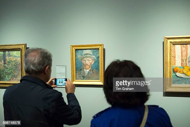 Visitor using smartphone to photograph self portrait by Vincent Van Gogh at Rijksmuseum Amsterdam Holland