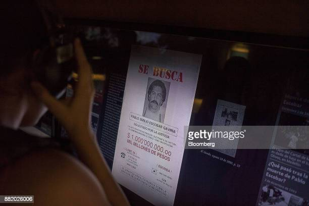 A visitor views a monitor displaying a wanted poster of narcotics kingpinPablo Escobar at the Museo Casa de la Memoria in Medellin Colombia on...
