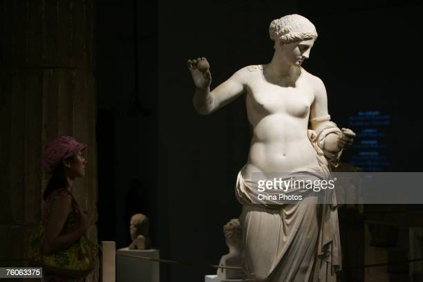 A visitor views a sculpture of Aphrodite during an exhibition of ancient Greek art from the Louvre Museum on August 11 2007 in Beijing China The...