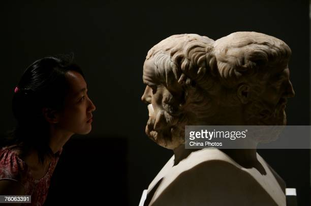 Visitor views a sculpture of Aristophanes and Sophocles during an exhibition of ancient Greek art from the Louvre Museum on August 11, 2007 in...