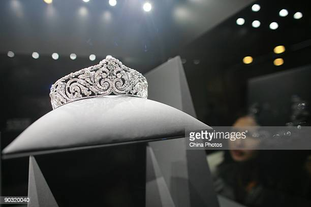A visitor views jewelry at the upcoming 'Cartier Treasures King of Jewelers Jewelers to Kings' exhibition in the Meridian Gate Gallery of Forbidden...
