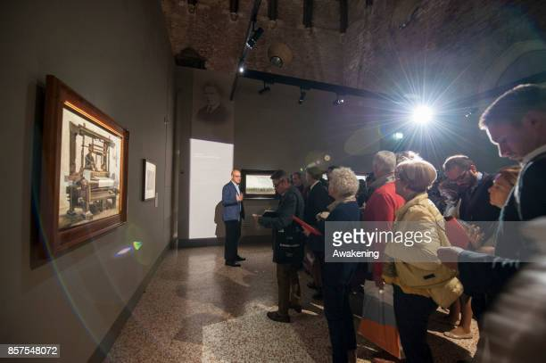 A visitor views paintings by Van Gogh inside at 'Van Gogh between the wheat and the sky' exhibition during the press preview on October 4 2017 in...