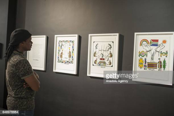 A visitor views paintings during South African artist Esther Mahlangu's exhibition of 1st President of South Africa Nelson Mandela at Melrose Art...