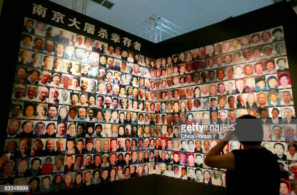 A visitor views pictures of Nanjing Massacre survivors during an exhibition of historical facts on the massacre at the National Museum August 10 2005...
