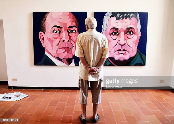 A visitor views the paintings by italian painter Giuseppe Veneziano entitled 'Silvio Berlusconi' and ' 'Totò Riina' at Palazzo Panichi which is...