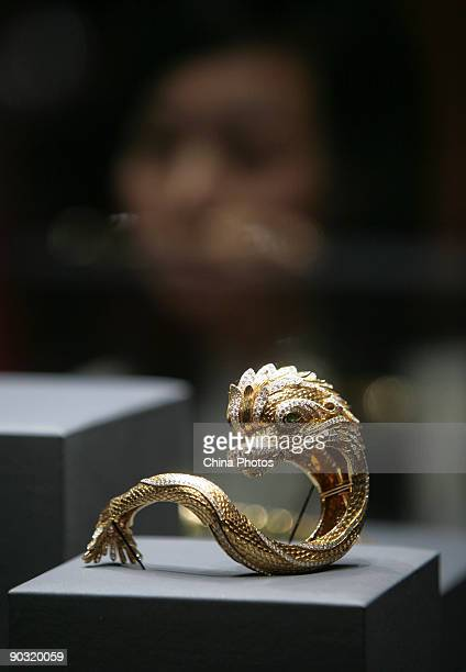 A visitor views treasures at the upcoming 'Cartier Treasures King of Jewelers Jewelers to Kings' exhibition in the Meridian Gate Gallery of Forbidden...