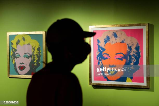 A visitor views two original screen prints of Marilyn Monroe by Andy Warhol both entitled 'Marilyn' at the 'Andy Warhol Pop Art' exhibition at the...
