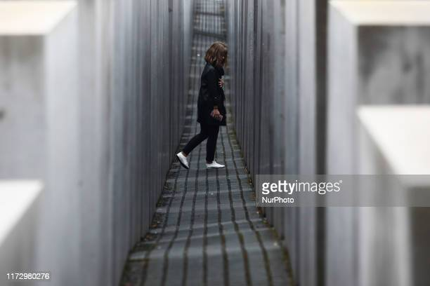 Visitor walk through the Holocaust Memorial, designed by Peter Eisenman, in Berlin, Germany on 25 September 2019.