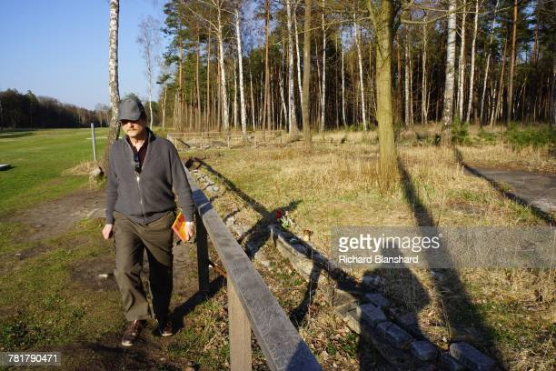 A visitor walking past structural remains at the site of the former BergenBelsen German Nazi concentration camp in Lower Saxony Germany 2014 Some of...