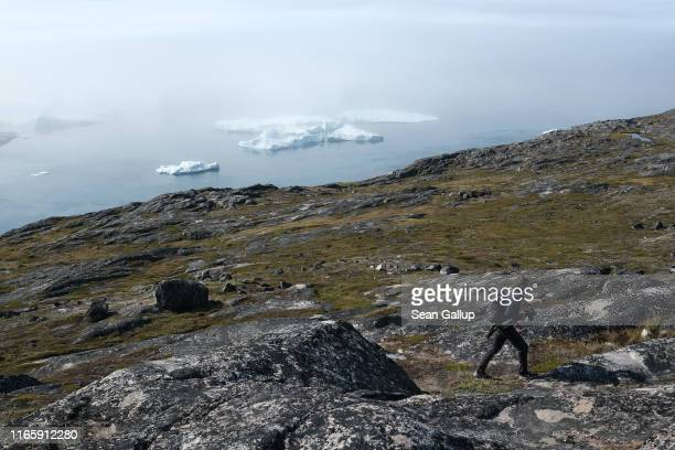 A visitor walks along a hillside near icebergs floating in the Ilulissat Icefjord in a bank of fog during a week of unseasonably warm weather on...