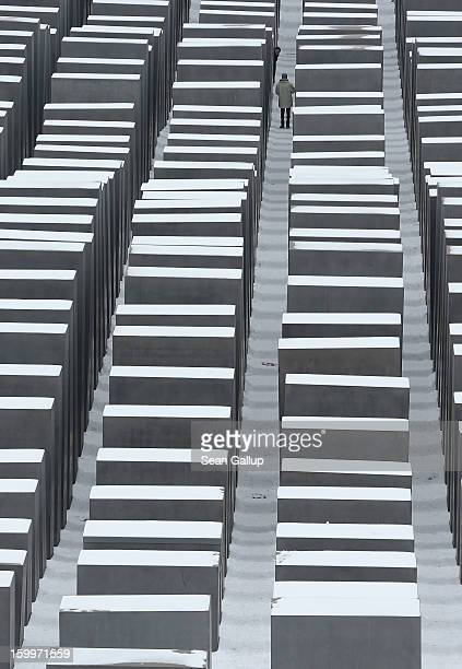 A visitor walks among snowcovered stellae at the Memorial to the Murdered Jews of Europe also known as the Holocaust Memorial on January 24 2013 in...