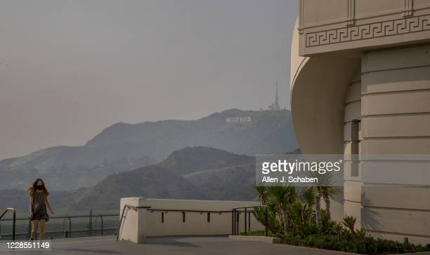 Visitor walks around the Griffith Observatory with a smokey/smoggy view of the Los Angeles skyline and Hollywood sign Monday, Sept. 14, 2020 in Los...