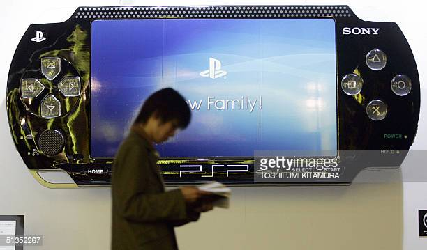 A visitor walks before a large display model of Sony's new PSP handheld game console during the Tokyo Game Show 2004 in Makuhari some 30 kilometres...
