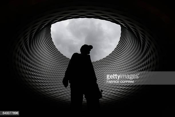 TOPSHOT A visitor walks beneath the roof of the exhibition hall designed by Swiss architecture firm Herzog de Meuron on June 14 2016 during the...