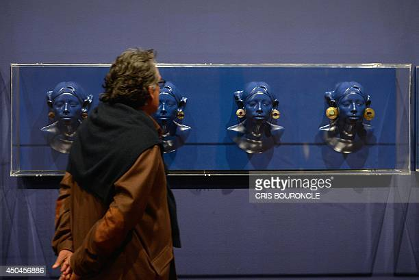 A visitor walks by a collection of metallic and other materials ear ornaments on display at the Art Museum of Lima on June 11 part of an exhibit that...