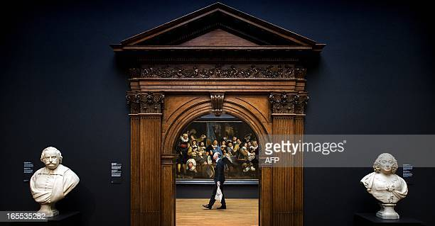 A visitor walks by a painting during a pressviewing day in The Rijksmuseum in Amsterdam on April 4 2013 Amsterdam's worldfamous Rijksmuseum which...