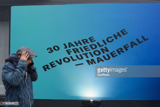 Visitor walks by a sign '30 Jahre friedliche revolution - Mauerfall' , seen near a part of a still-standing section of the former Berlin Wall called...