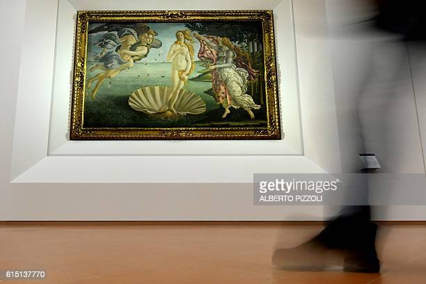 A visitor walks by 'The birth of Venus' painted in the mid 1480s by Italian painter Sandro Botticelli during a press preview for the reopening of the...