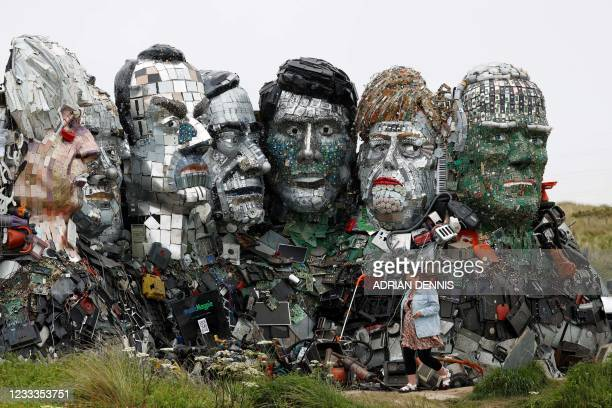 Visitor walks in front of a giant Mount Rushmore-style sculpture of the G7 leaders heads, made entirely of discarded electronics, on a beach near to...