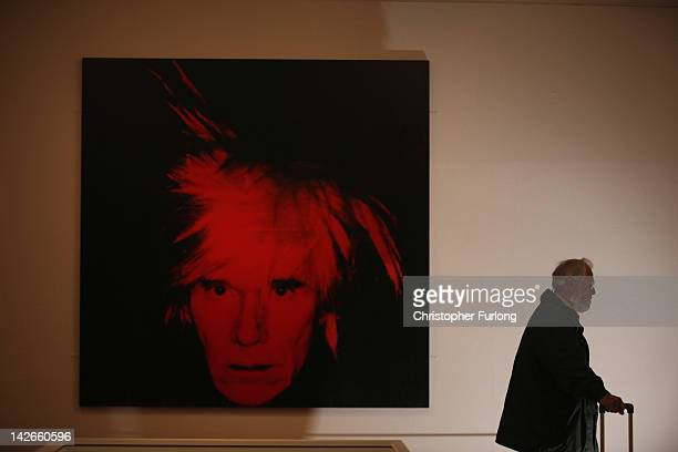 A visitor walks near SelfPortrait 1986 by artist Andy Warhol at the Graves Gallery on April 11 2012 in Sheffield England The exhibition 'Andy Warhol...