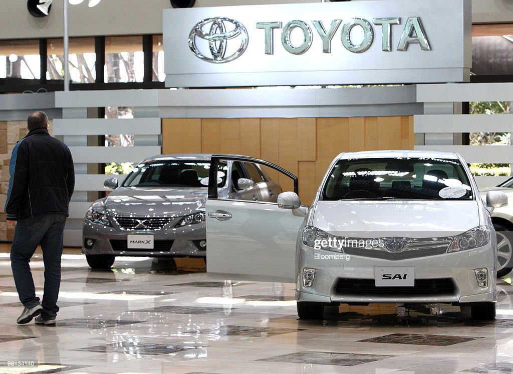 A visitor walks near Toyota Motor Corp.'s Sai hybrid vehicle, right, and Mark X sedan at the company's showroom in Toyota City, Japan, on Tuesday, March 30, 2010. Toyota Motor Corp.'s accelerator flaws and electronic vehicle controls will be examined by NASA as the U.S. expands its probe into incidents linked to at least 51 deaths. Photographer: Tomohiro Ohsumi/Bloomberg via Getty Images
