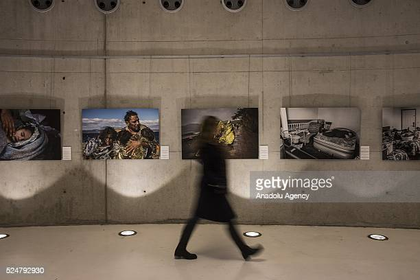 A visitor walks next to story news first prize awarded European Dream photo series at Istanbul Photo Awards 2016 as Anadolu Agency opens first...