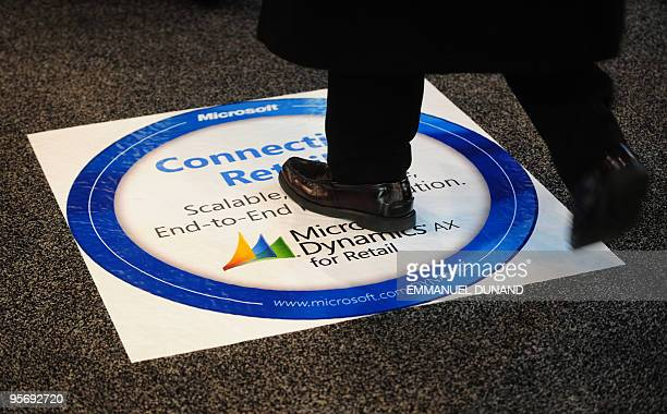 A visitor walks on an advertisment for soontobe released Microsoft Dynamics AX for Retail solution during the 2010 National Retail Federation Big...