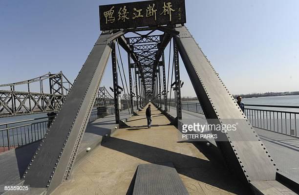 A visitor walks on 'Broken Bridge' in Dandong on March 23 2009 which used to connect China and North Korean before it was bombed by the US during the...