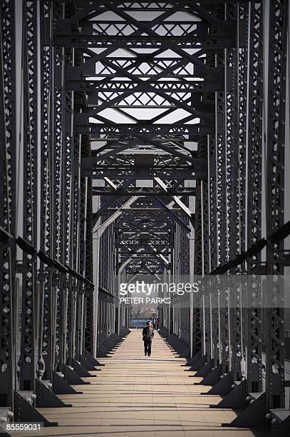A visitor walks on Broken Bridge in Dandong on March 23 2009 which used to connect China and North Korean before it was bombed by the US during the...