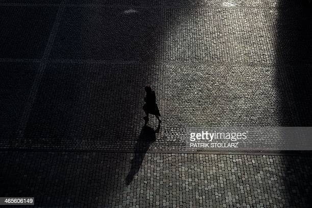 A visitor walks over the court of the cathedral of Aachen western German on January 28 2014 STOLLARZ