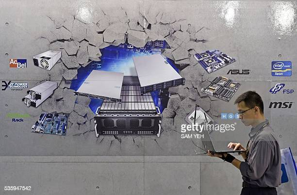 A visitor walks pass a wall painted with various information technology products the annual Computex computer exhibition in Taipei on May 31 2016...