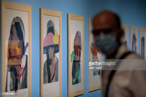 A visitor walks past 10 screen prints entitled 'Ladies and Gentlemen' by Andy Warhol at the 'Andy Warhol Pop Art' exhibition at the RCB Galleria on...
