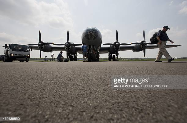 Visitor walks past a B-29 bomber after it took part in a practice flight with dozens of World War II era aircraft at Manassas Regional Airport,...