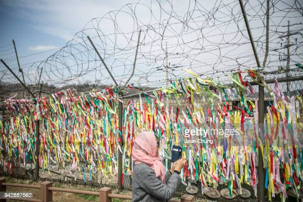 A visitor walks past a barbed wired fences at the fortified Demilitarised Zone on April 7 2018 in Paju South Korea On April 27 South Korean President...