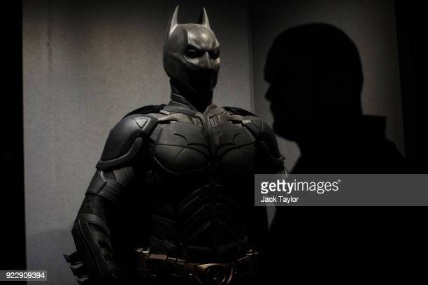 Visitor walks past a Batman costume from the 2012 Dark Knight Rises film worn by Christian Bale and designed by Lindy Hemming is on display at the DC...