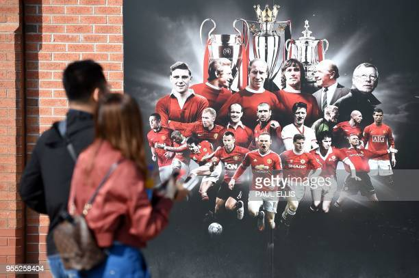 A visitor walks past a billboard featuring football greats including legendary football manager Sir Alex Ferguson outside the Manchester United...