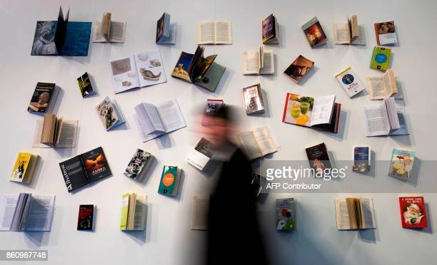 Visitor walks past a book display at the Frankfurt Book Fair on October 13, 2017 in Frankfurt am Main, western Germany. France is this year's guest...
