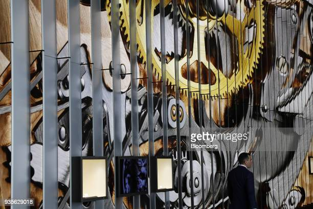 A visitor walks past a booth during the opening day of the 2018 Baselworld luxury watch and jewelry fair in Basel Switzerland on Wednesday March 21...